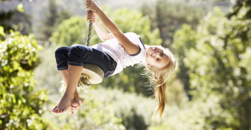 Young girl leaning back on rope swing in sunshine