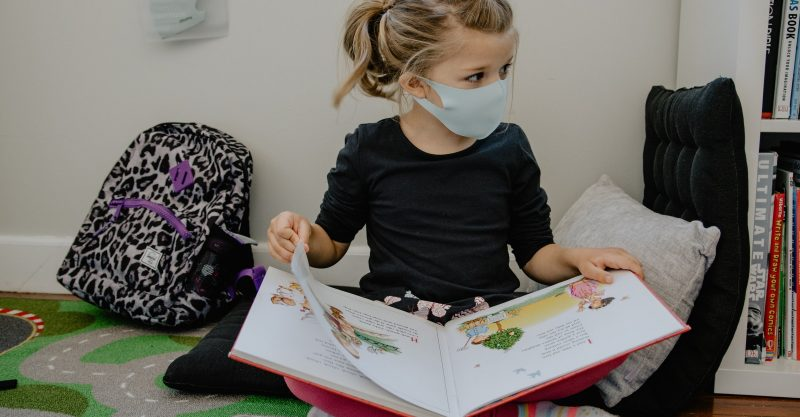Young girl wearing a mask in a classroom.